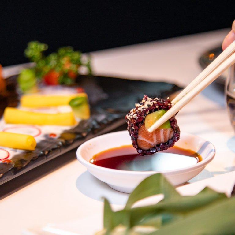 Dettaglio di Uramaki con riso venere in ciotola di salsa di soia, con bacchette