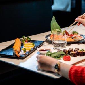Tavolo imbandito di sushi e sashimi con persona che mangia con bacchette